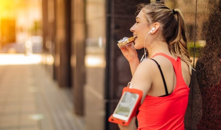 Woman eating a protein bar after workout